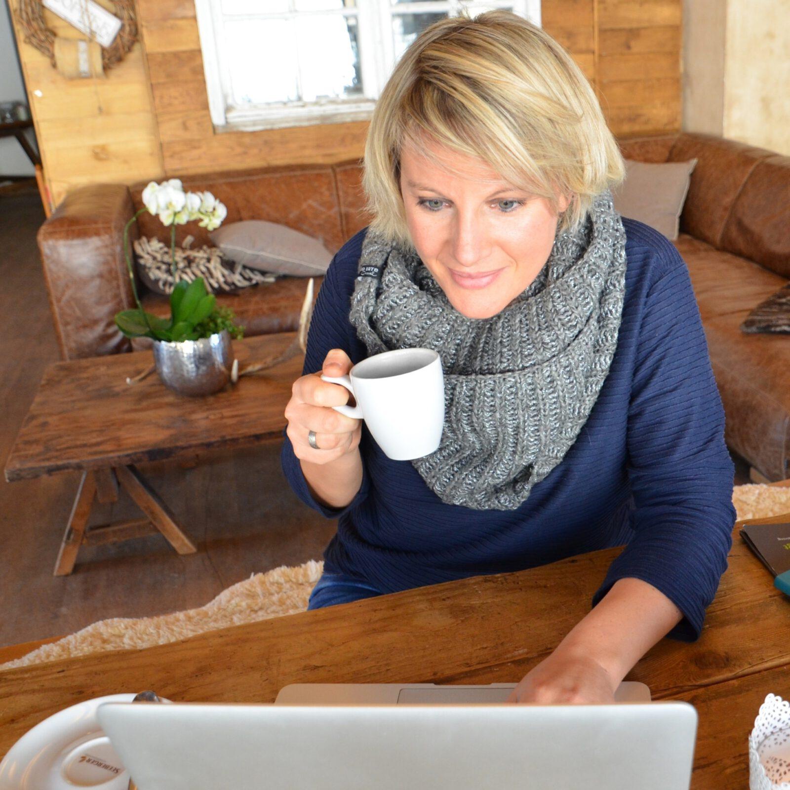 Katja Voigt arbeitet mit einer Tasse Kaffee in der Hand am Laptop